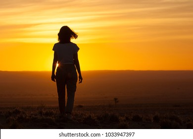 A woman walking towards the sunset in the Namibia desert