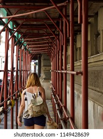 a woman is walking under a scaffolding