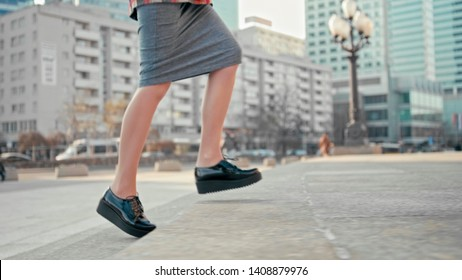 Woman Walking Upstairs Outdoors in City. Female Legs in Pencil Skirt and Patent Platform Shoes Making Steps Up to Climb Up the Stairs