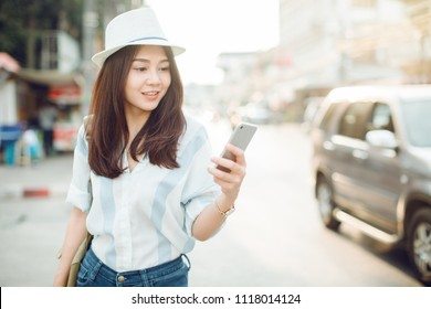 Woman walking and using a smart phone in the street in a sunny summer day