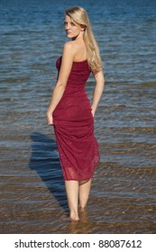 A woman walking in the water in her red formal looking over her shoulder.