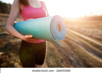 woman walking with a yoga mat outside during sunset n a rural area wearing sports wear and doing yoga