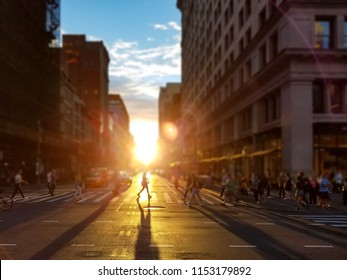 Woman walks across an intersection on 5th Avenue in Manhattan New York City as the summer sunset in the background casts long shadows in the street