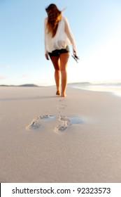 a woman walks along an empty beach leaving footprints in the sand