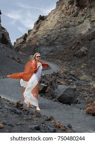 woman walks along a path in volcanic terrain