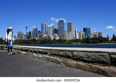 Woman walks along Sydney skyline in New South Wales, Australia.