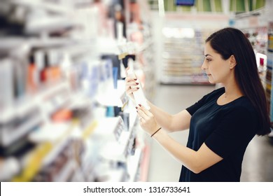 woman walks around the store and examines the goods on the shelves