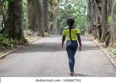 Woman walks away against new discoveries in a park located in Accra Ghana. Aburi Botanical Gardens is about 30 min north of the city of Accra.