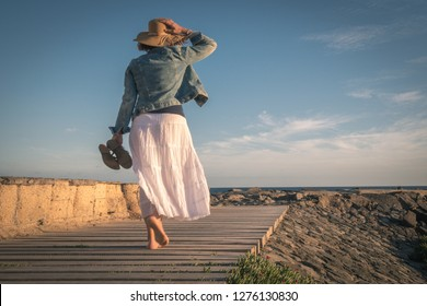 Woman walks barefoot on the floor of wooden planks facing the ocean, long white skirt holds back in the wind straw hat in the other hand leather sandals jacket jeans stone wall stone blue and pink sky
