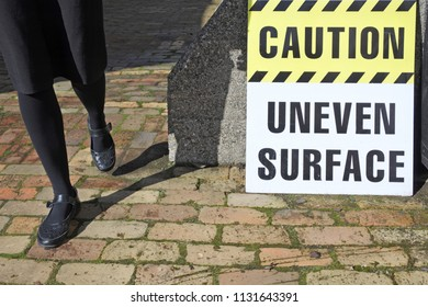 Woman walks beside Caution - Uneven Surface. Danger concept. Copy space