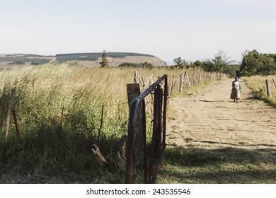 A woman walks down a dirt path alone