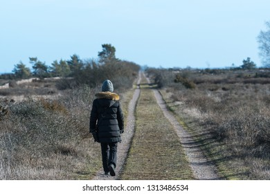 Woman walks in fall season on a sunlit country road