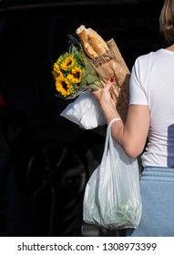 A woman walks having shopped for baguette and sunflowers in Cassis, France