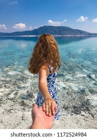 Woman walks holding the photographer's hand leading to the lake located in the Salda lake (Salda Gölü) in Burdur, Turkey