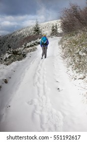 a woman walks and leaves footprints in the snow, young woman with a backpack walking along the trail in the mountains on the background of snowy mountains and cloudy sky.