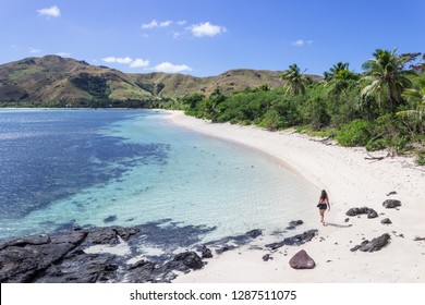 """A woman walks on the beaches of Nacula Island. Tropical and desolate paradise, was the scenery of the famous Film called """"The Blue Lagoon"""" in year 1980. Fabulous tourist destination in Yasawa, Fiji."""
