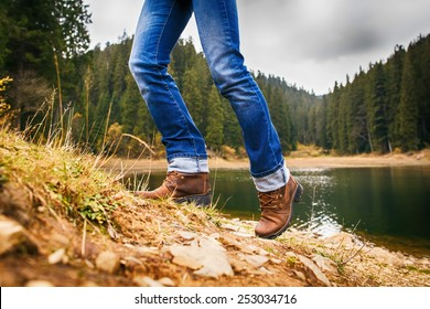 Woman walks up on hill in forest