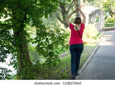 Woman walks on a sidewalk curb in the street