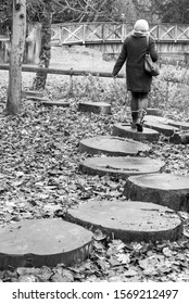A woman walks on some wooden stepping stones made out of old tree trunks