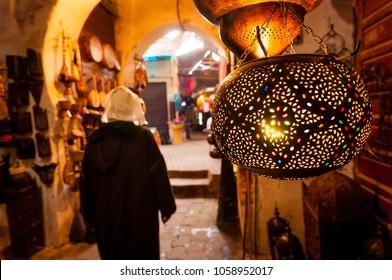 A woman walks past a lantern shop in a Marrakech souk.