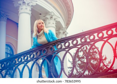 Woman walks in the spring through the city streets in a blue coat with a good mood in anticipation. Blonde lady in a coat and a knitted sweater, jeans in the style of casual