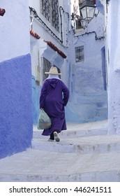 A woman walks through medina in Chefchaouen, Morocco