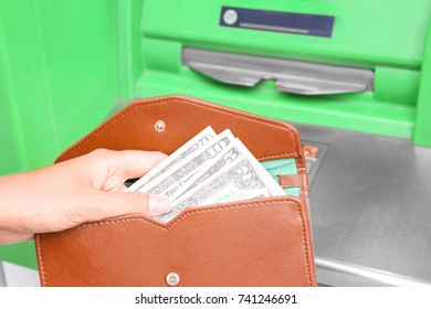 Woman with wallet and money near cash machine, closeup