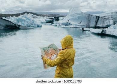 woman wanderer searching direction on location map in Iceland near glacial lagoon