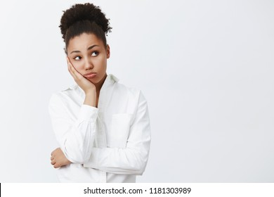 Woman wants go home, waiting clock ring to leave office. Portrait of dreamy tired and bored cute african-american female office worker, leaning on palm and gazing right, feeling boredom