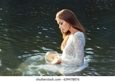 Woman wants to release the goldfish into the water.