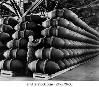 Woman war worker checks 1,000 lb. bomb cases loaded with explosives. Firestone Tire and Rubber Co., Omaha, Nebraska. May 1943 during World War 2.
