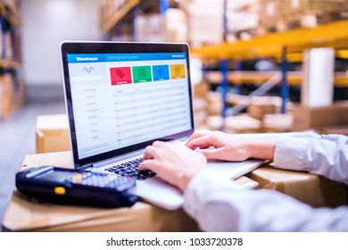 Woman warehouse worker or supervisor with laptop