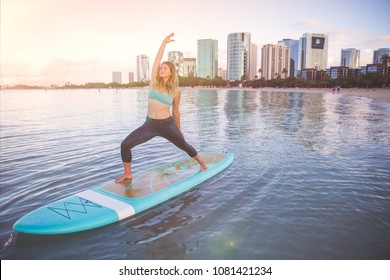 Woman in warior pose loving SUP Yoga practice sunrise in Waikiki