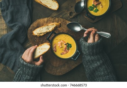 Woman in warm grey sweater eating corn creamy chowder soup with prawns served in individual pots, top view. Woman' s hand keeping spoon and bread slice. Flat-lay of rustic dinner table. Slow food
