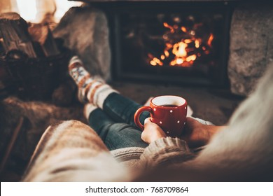 Woman in warm knitted cardigan sweater by fireplace. Woman relaxes by warm fire with a cup of hot drink and warming up her feet in woollen socks. Cozy atmosphere. Winter and Christmas holidays concept