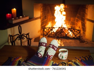 A woman in warm knitted socks with a cup of hot punch in front of the fireplace