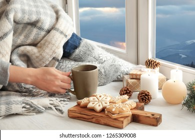 Woman in warm socks with hot drink and Christmas cookies enjoying view of winter mountain landscape from window at home