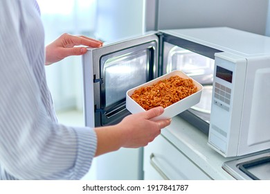 Woman warming up a container of food in the modern microwave oven for snack lunch at home