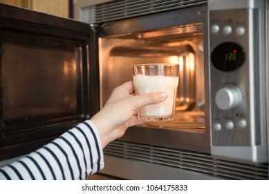 woman warming a glass of milk in the microwave