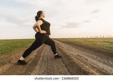 Woman warming up legs before outdoor running. Getting ready for jogging. Sport, activity, healthy lifestyle and weight losing