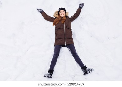 Woman warmly clothed in a cold winter forest makes snow angel figure at park. Copy space text.