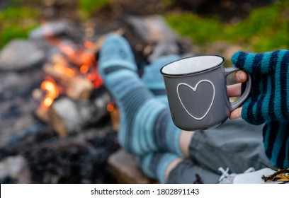 Woman warms feet in socks around bonfire and holds cup of a hot tea