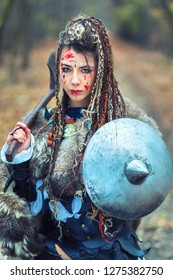 Woman warrior with braided hair and painted face holding ax and shield looking dangerous, Outdoor warrior princess with blood on face wearing fur alone in woods after atack or raid – cinematic filter