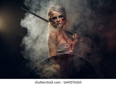 Woman warrior wearing rag cloth stained with blood and mud posing with a sword and shield. Studio photo on a dark background with smoke. Cosplayer as Ciri from The Witcher