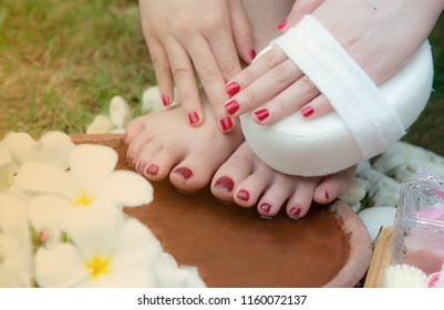 Woman washes and cleans the feet in water clearing sponge and frangipani flowers in the garden,pink beige towels,Soap,Massage brush,Cosmetic bottles,Natural color,foot massage,spa,Health care,