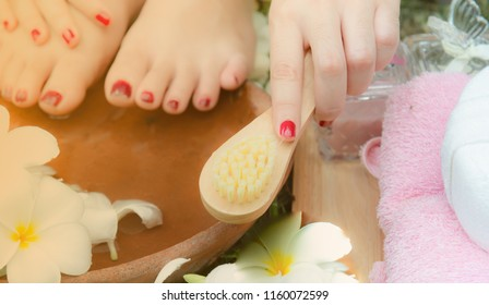 Woman washes and cleans the feet in water clearing foot scrub frangipani flowers in the garden,pink beige towels,Soap,Massage brush,Cosmetic bottles,Natural color,foot massage,spa,Health care,