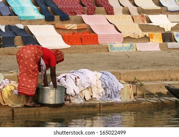 A woman washes clothes next to the Ganges River, in Varanasi, India.  Clothes seem to come out clean, although the river is extremely polluted.