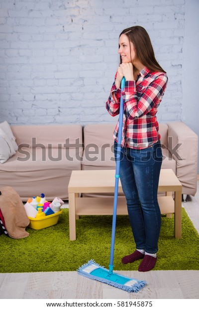 woman washes the floor, holding mop in her hand, standing in room. Household chores