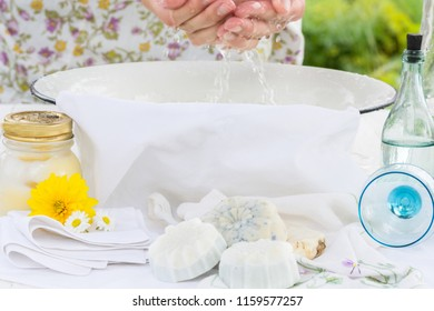 Woman washes her face and hands in the white bowl outdoors, nearby are handmade soaps, flowers and cream, cleanliness and hygiene concept