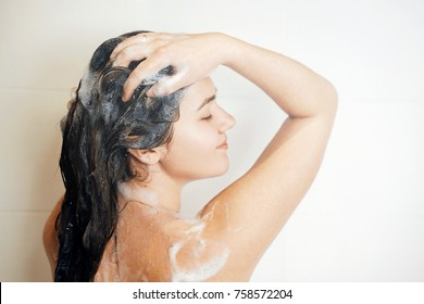 woman washes her hair in shower, stands back to camera, takes a shower, steam coming, foam on hair